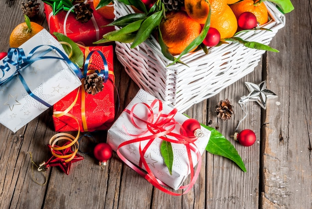 Christmas and new year concept. fresh tangerines with green leaves in a white basket, christmas decoration and gift boxes, on old rustic wooden table,