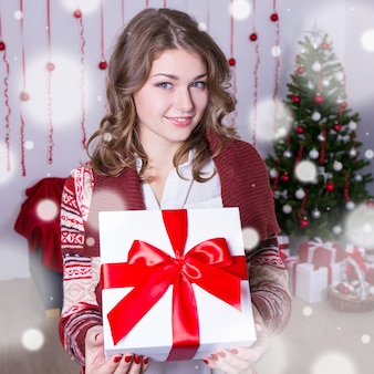 Christmas and new year concept - portrait of happy young woman holding present box in decorated room