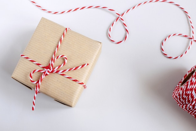 Christmas or new year concept - present box in craft paper with twisted red and white cord.