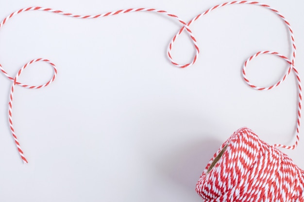 Christmas or new year concept - twisted red and white cord isolated, white