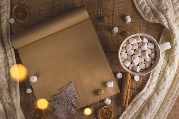 Рождество новый год концепция с чашкой кофе с зефиром и блокнотом. с копией пространства. шарф, фары