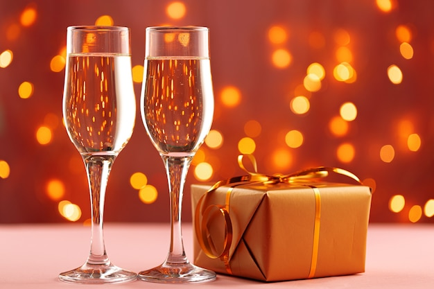 Christmas and new year concept with glasses of champagne against bokeh lights