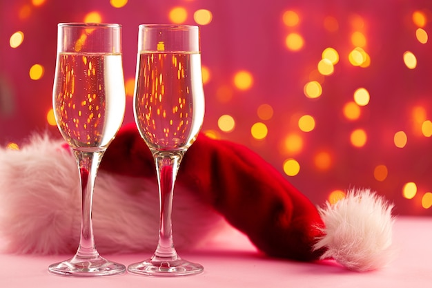 Christmas and new year concept with two glasses of champagne against bokeh lights background