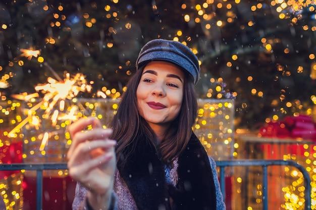Christmas, new year concept. woman burning sparkler by christmas tree on city street fair. holiday season