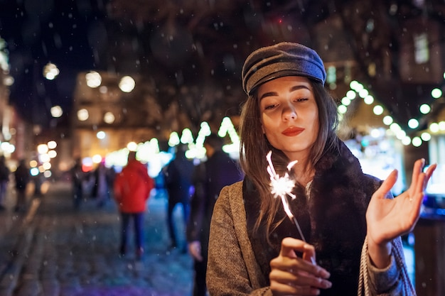 Christmas, new year concept. woman burning sparkler on city street fair. girl holding paper bags with presents. holiday shopping