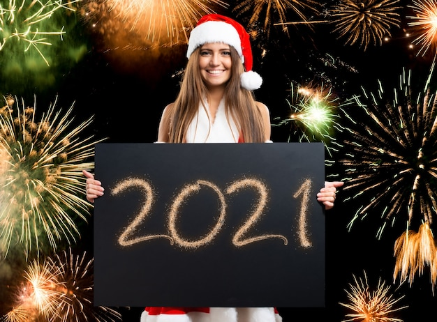 Christmas and new year concept, woman holding a happy 2021 wishes card