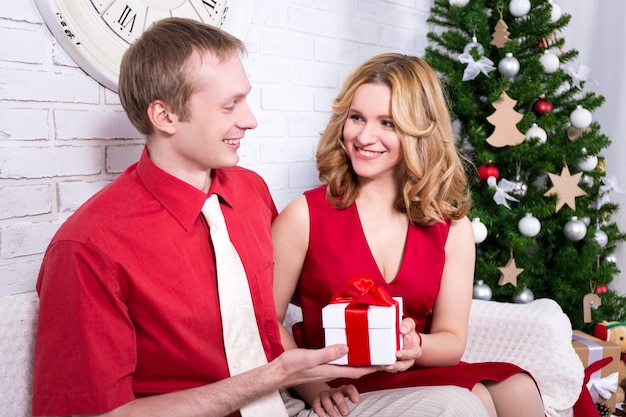 Christmas and new year concept  young lovely couple exchanging gifts