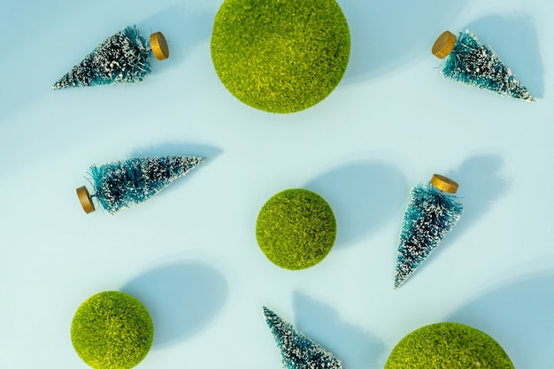 Christmas and new year conceptual background with small christmas trees and green balls on blue background. trendy hard shadows, studio shot.