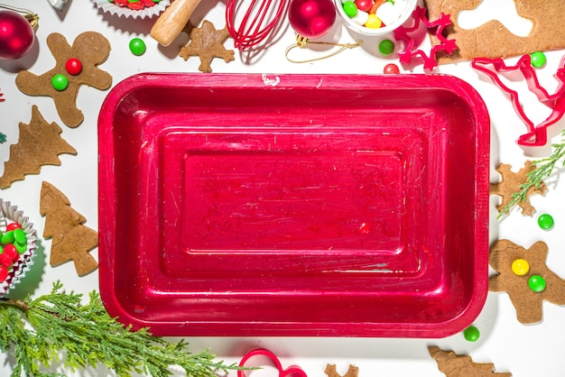 クリスマス、新年の料理の背景。ベーキング材料と調理器具-ジンジャーブレッド生地、クッキーカッター、めん棒。お祝いのクリスマスの甘いクッキーを明るくお祝いの赤白のコンセプトにする