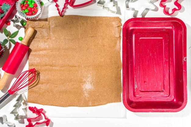 Christmas, new year cooking background. baking ingredients and utensils - gingerbread dough, cookie cutters, rolling pin. making festive christmas sweet cookies bright festive red white concept