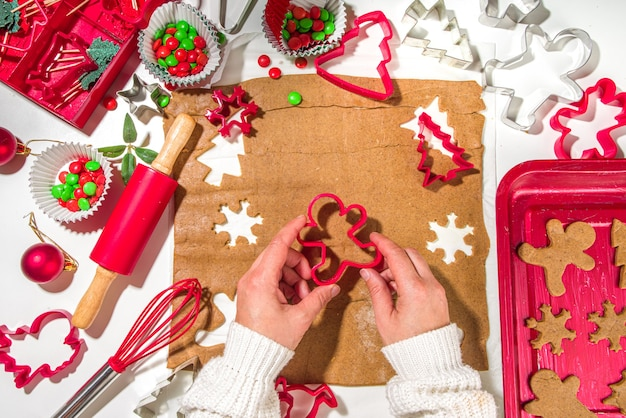 Christmas, new year cooking background. baking ingredients and utensils - gingerbread dough, cookie cutters, rolling pin. woman hands making festive xmas sweet cookies bright festive red white concept