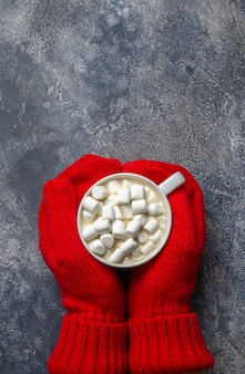 Christmas and new year cozy holiday composition with scarf, woman hands in mittens, mugs with hot drink and marshmallow on the gray concrete background. flat lay, top view.
