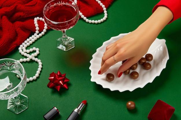 녹색 테이블에 여자 손과 빨간 샴페인 한 잔과 함께 크리스마스 새해 창조적 인 구성