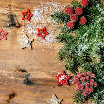 Christmas new year creative layout or greeting card with fir tree branches, red berries and stars over wooden background. flat lay, copy space, square image