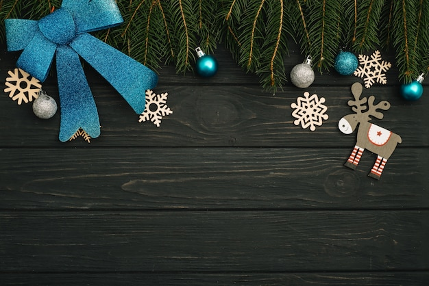 Christmas or new year dark wooden background, xmas black board framed with season decorations, view from above