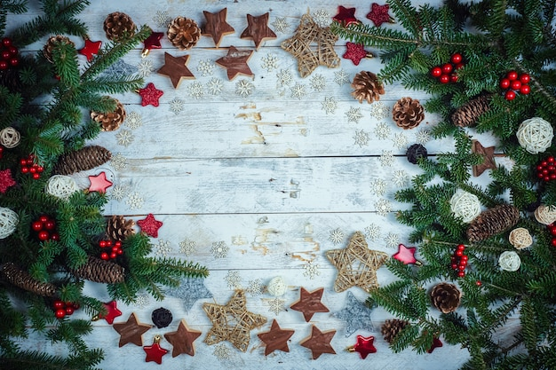 Christmas or new year decoration background: fir-tree branches on a wooden background with copy space.