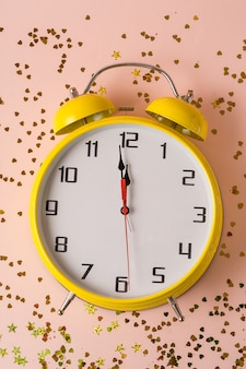 Christmas and new year decorations and greeting card with retro style alarm clock on confetti .
