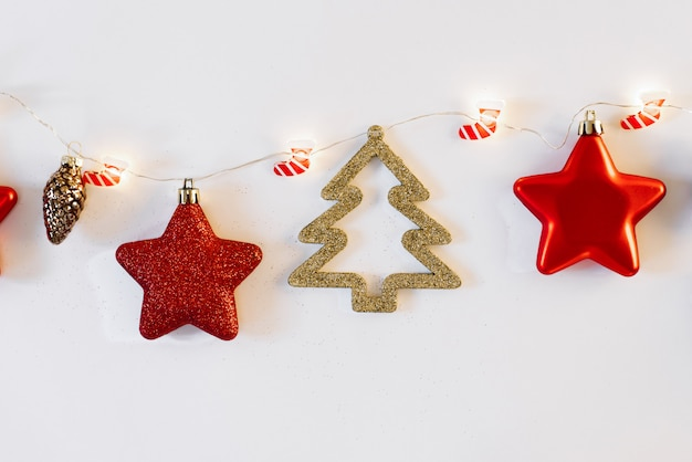 Christmas or new year feat lay. stylish greeting card. christmas toys on a ribbon with lights