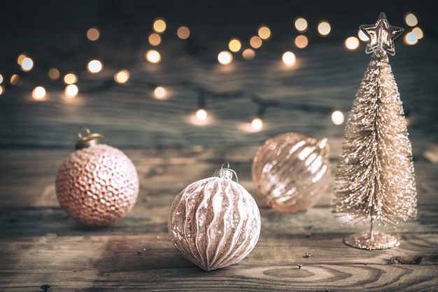 Christmas or new year festive background, vintage toys on the christmas tree on a wooden background with a garland with lights