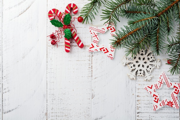 Christmas or new year. fir-tree branches , christmas tree toys, stars, snowflake and cones on white wooden.