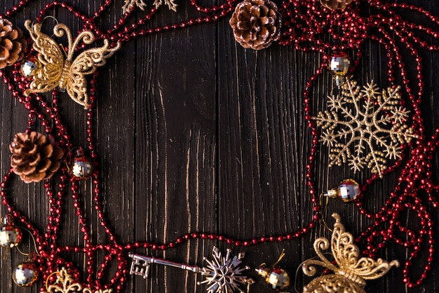 Christmas or new year frame. christmas branches, fir cones and red necklace on wooden boards