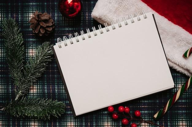 Рождество новогодняя рамка в стиле flatley с видом сверху с елочными украшениями из шишек, еловые ветки на фоне в клетке, место для вашего текста