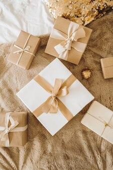 ベッドの上のクリスマス、新年のギフトボックス。最小限の冬休みお祭り
