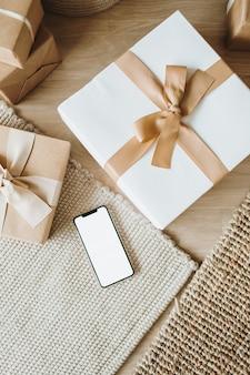 弓が付いているクリスマスの新年のギフトボックス。空白のコピースペースのモックアップ画面を備えたスマートフォン。伝統的な冬の休日のギフトパッケージの創造的な概念