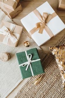 弓が付いているクリスマスの新年のギフトボックス。伝統的な冬の休日のギフトパッケージの創造的なコンセプト。