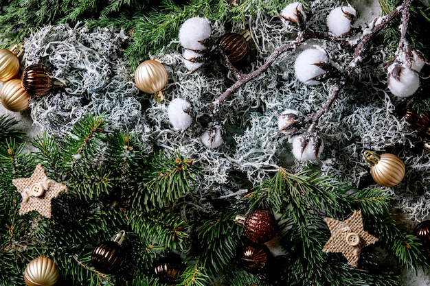 Christmas new year greeting card background with fir tree branches, moss, golden balls and stars