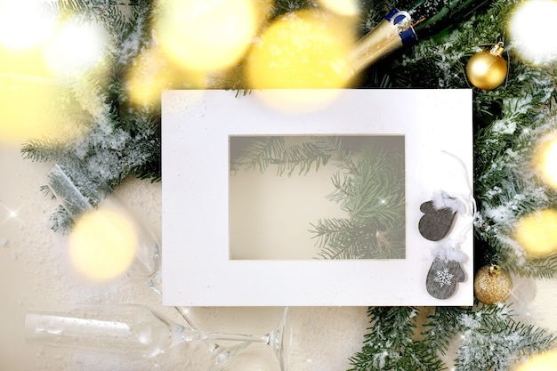 Christmas or new year greeting card with fir tree branches with golden christmas ball, glasses and bottle of champagne, white paper frame. golden bokeh light. beige background. flat lay, copy space
