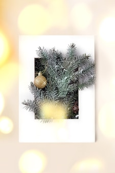 Christmas or new year greeting card with fir tree branches with golden christmas ball in white paper frame. golden bokeh light. beige background. flat lay, copy space