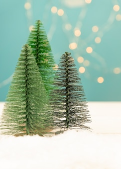 Christmas or new year greeting card with toy fir trees on blue bokeh