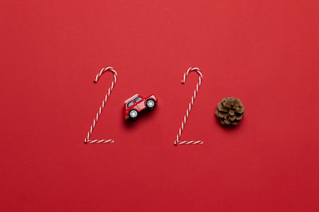 Christmas and new year holiday 2020 lettering of various decoration red car toy, fir cone on a red background