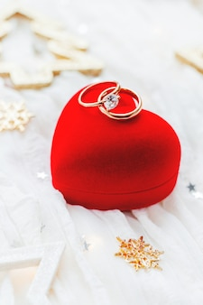 Christmas and new year holiday background with decorations and wedding rings on gift heart box.