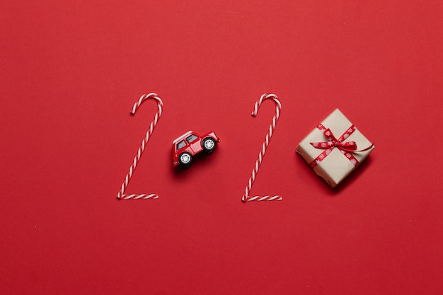 Christmas and new year holiday composition 2020 lettering of various decoration red car toy, gift box