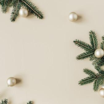 クリスマス年末年始の構成。空白のコピースペース、モミの針の枝、ベージュのクリスマスつまらないものでフレームをモックアップ