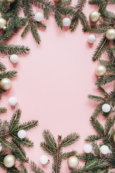 クリスマス年末年始の構成。空白のコピースペース、モミの針の枝、ピンクのクリスマスつまらないものでフレームをモックアップ