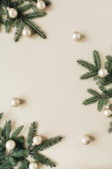 クリスマス年末年始の構成。モミの針の枝とベージュのゴールドのクリスマスボールで作られた空白のコピースペースでフレームをモックアップ