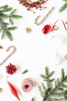 クリスマス年末年始の構成。空白のコピースペース、モミの針の枝、クリスマスつまらないもの、お菓子、白の装飾とモックアップフレーム