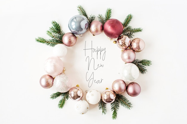 Рождество новый год праздничный состав. цитата «с новым годом» в рамке венок с елочными шарами, шарами и еловыми ветками на белом