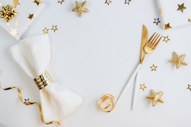 Christmas and new year holiday table setting on white background with golden decorations.
