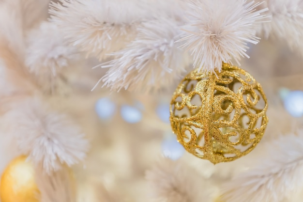 Christmas and new year holidays background. white christmas tree decorated with white and gold balls. celebration concept