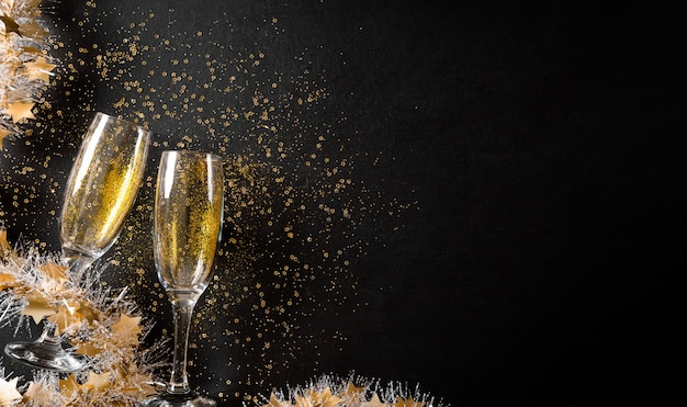 Christmas and new year holidays wall concept made from champagne glasses with golden glitter on black wooden wall.