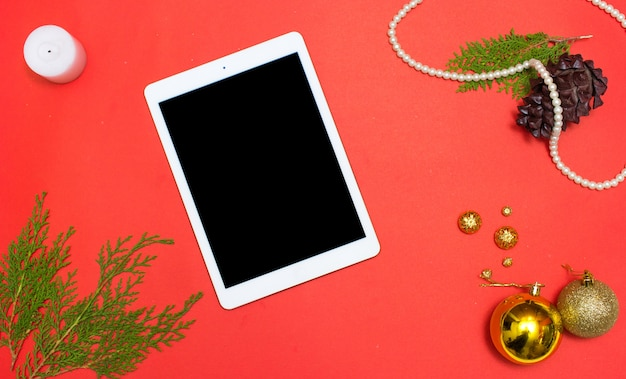 Christmas or new year ipad tablet background: fir tree branches, gold glass balls, decoration and cones