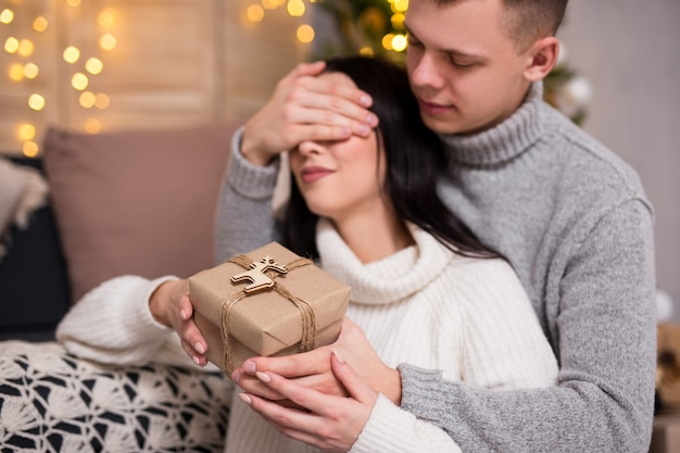 Рождество, новый год, концепция любви и сюрприза - молодой человек удивляет свою девушку рождественским подарком дома