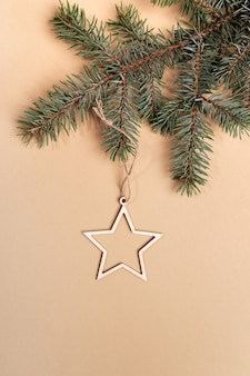 Christmas or new year minimal layout with green fir tree twig and festive decoration - xmas toy - wooden star on beige with copy space. top view. vertical orientation.