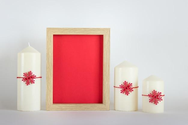 크리스마스, 새해 모형, 빨간색 배경이 있는 빈 프레임, 흰색 배경에 흰색 촛불 3개, 빨간색 눈송이가 있는 템플릿.