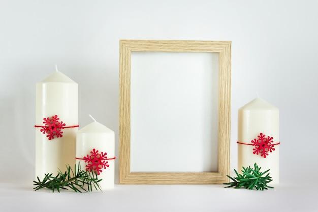 크리스마스, 새해 목업 템플릿에는 나무 프레임과 흰색 배경에 녹색 전나무와 붉은 나무 눈송이가 있는 흰색 촛불 3개가 있습니다.