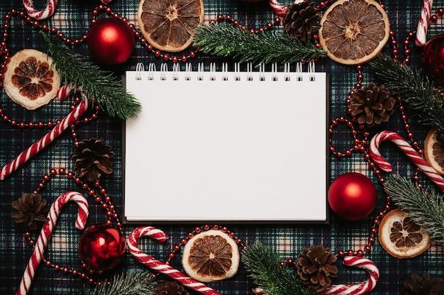 Рождество новый год бумажная рамка, плоский стиль с видом сверху с рождественскими украшениями из шаров, конусов, рождественских тростей, еловых веток на фоне в клетке. место для вашего текста